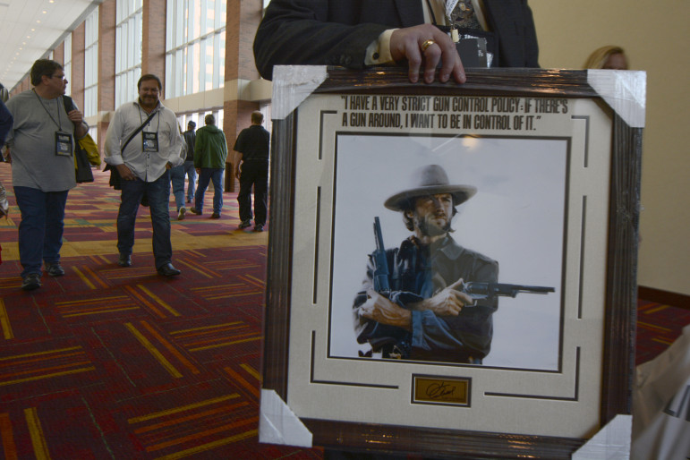 An NRA member carries a framed picture of Clint Eastwood from the exhibit hall at the group's 143rd annual convention. Photo by Jacob Byk/News21.
